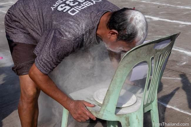 man blowing powder to find a coin