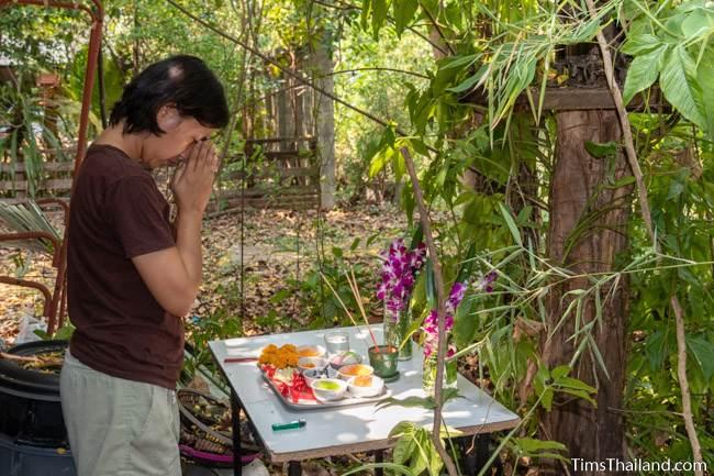 praying before a spirit house