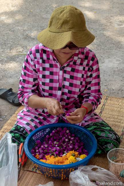 woman preparing flowers for sand stupas