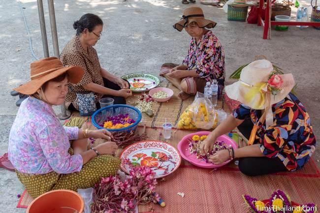 women preparing flowers for sand stupas
