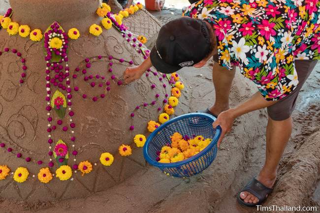 woman putting flowers on sand stupa