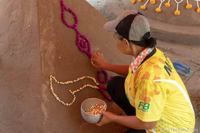 woman putting flowers on sand stupa