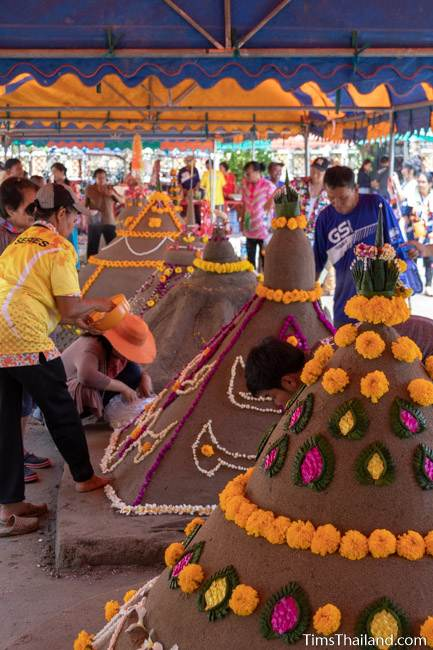 women putting flowers on sand stupa