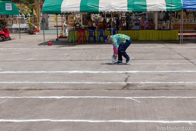 man putting chalk on the group to make a racetrack