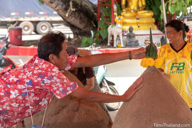 man putting flowers atop a sand stupa