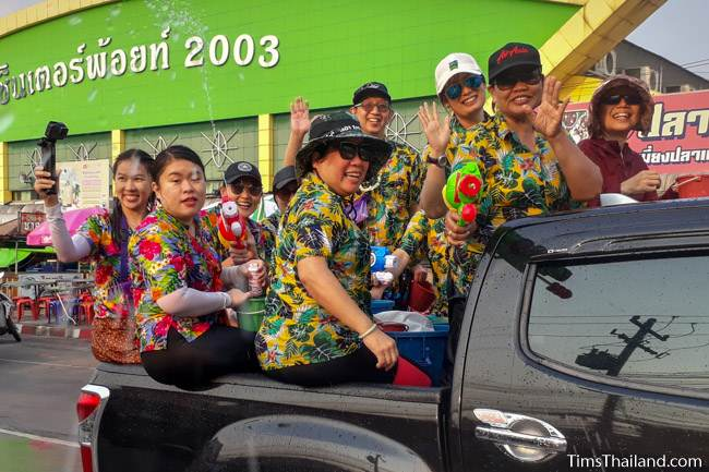 people in colorful shirts sitting in back of a pickup truck