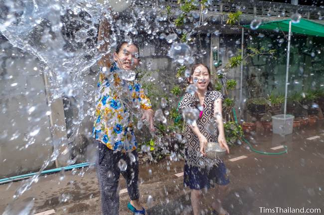 children throwing water at the photographer