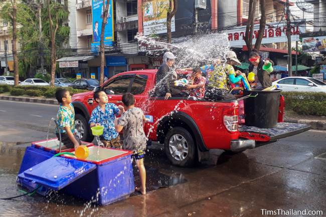 people on the street and in a truck throwing water at each other