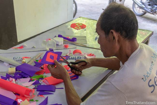 man cutting paper for a parade float