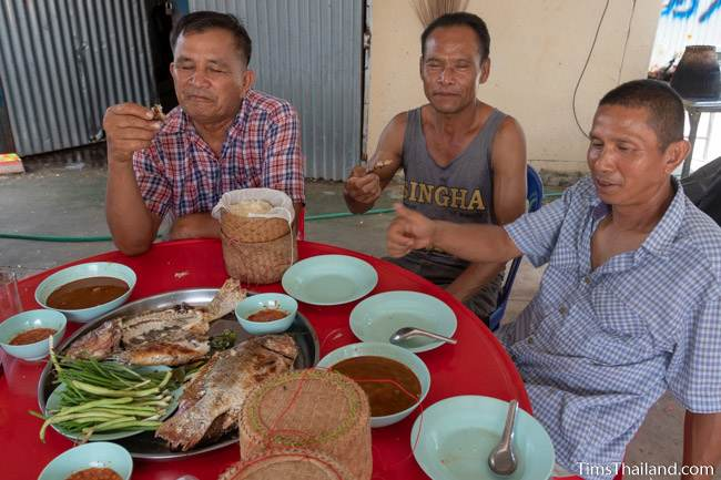 men at a table eating grilled fish with sticky rice