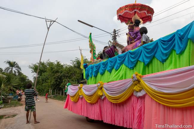 man with bamboo pole lifting power line to let parade float pass under