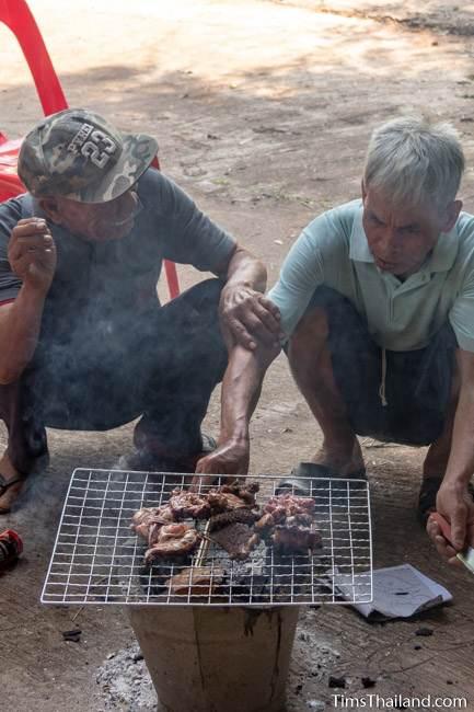 men grilling meat