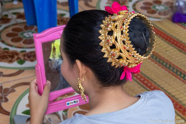 woman looking at her makeup in a mirror