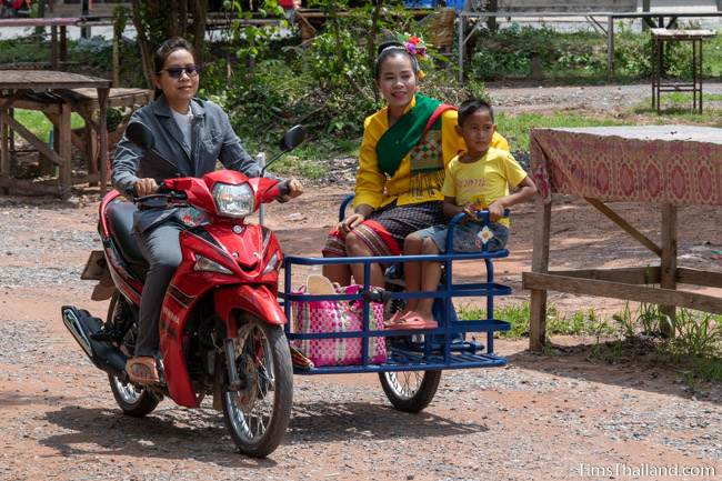 woman in traditional Thai dress riding in a motorcycle sidecar