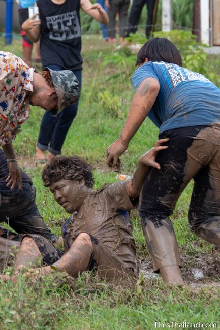 man pushing friend into mud