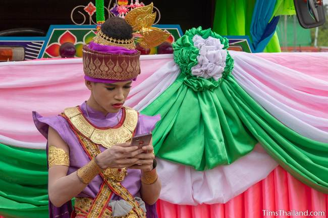 boy in traditional Thai dress on his phone