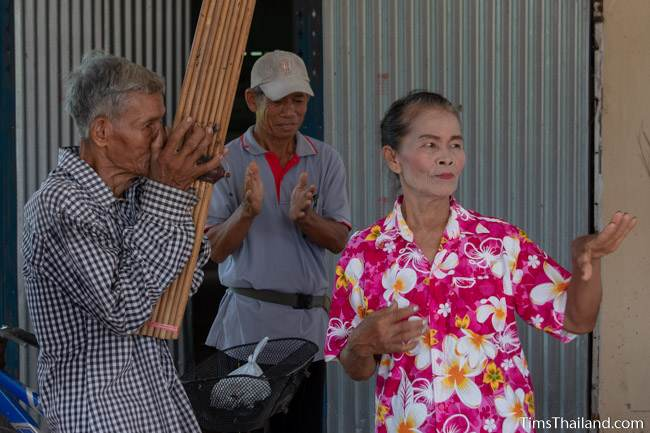 man playing the kaen and a woman dancing