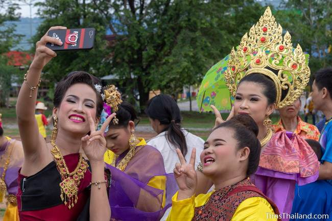 women in traditional Thai clothes taking a selfie