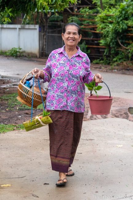 woman carrying kratong, food basket, and water bucket