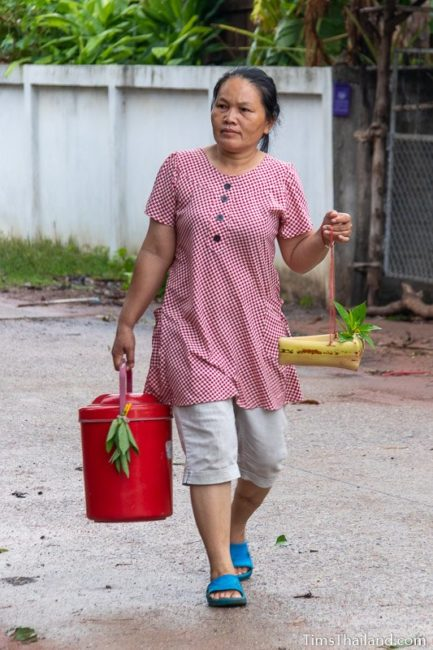 woman carrying kratong and water bucket
