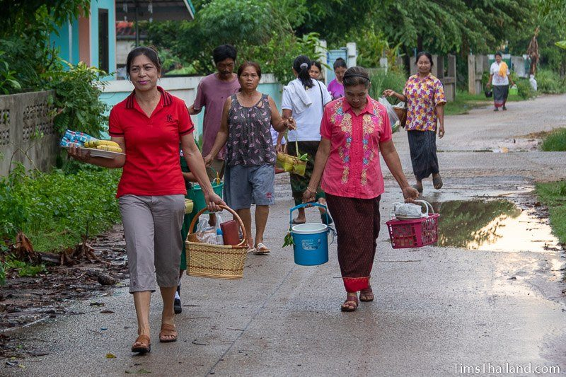 women carrying kratong, food baskets, and water buckets