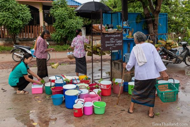 women delivering kratong and water buckets