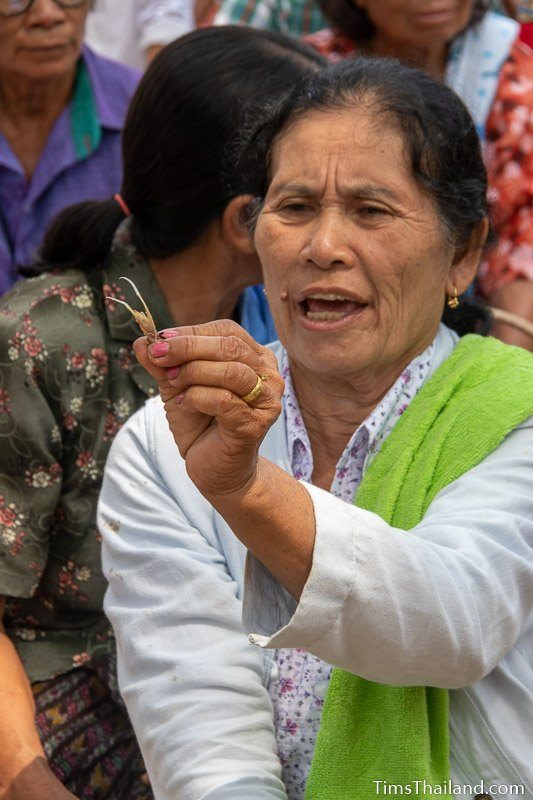 women holding chicken bone up for people to see