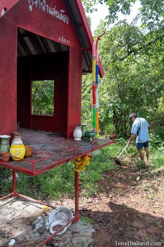 man with hoe clearing ground next to shrine