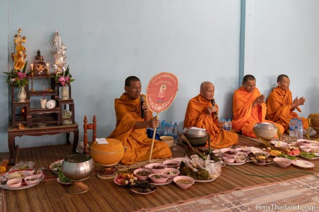 monks chanting with trays of food in front of them