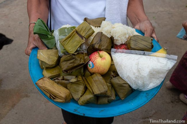 woman holding tray of fruit, rice, and snacks in banana leaves