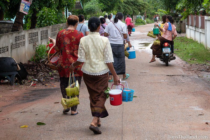 women walking home with kratong and water buckets after ceremony