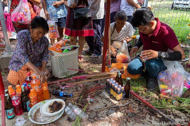 putting drink offerings on ground under shrine