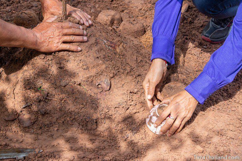 women making dirt stupa