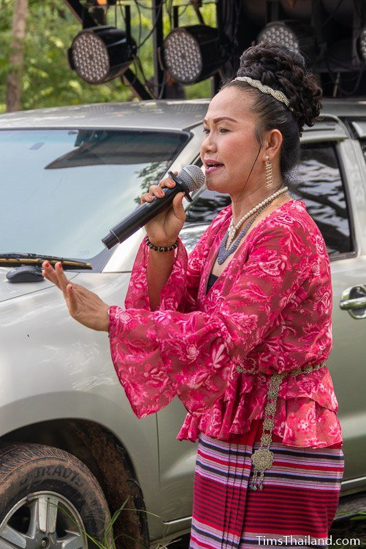 woman singing in front of truck with large PA system