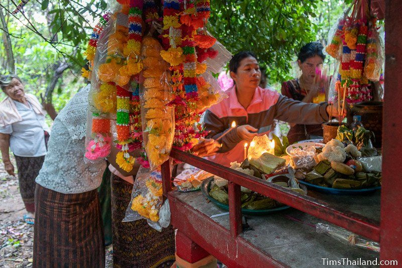 women putting food on a shrine