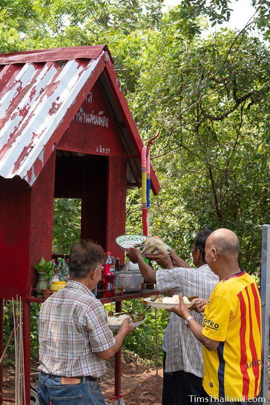men putting food on a shrine