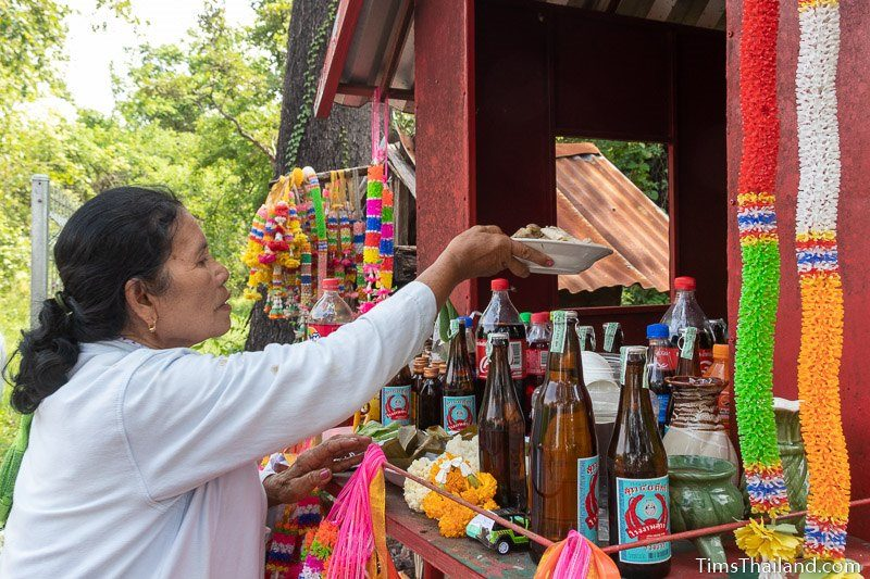 woman putting food in a shrine