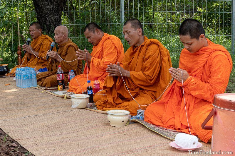 monks holding white string