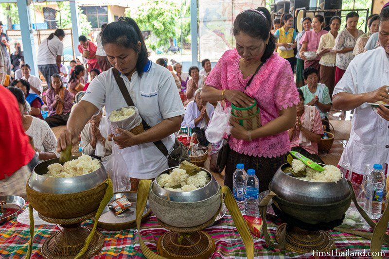 people putting food in monk alms bowls