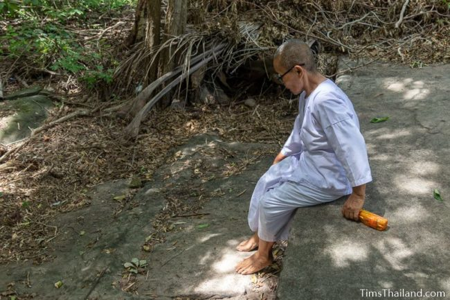 Buddhist nun sitting on long sandstone cutting edge in bedrock