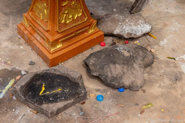 three pieces of sandstone on ground in front of village shrine