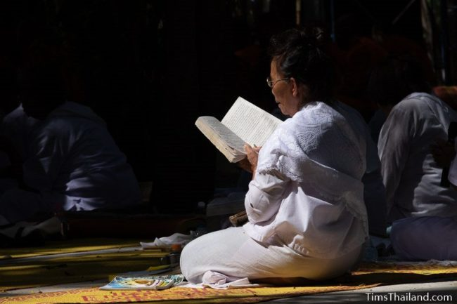 woman in white reading a chanting book