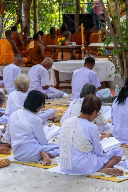 monks and people in white chanting