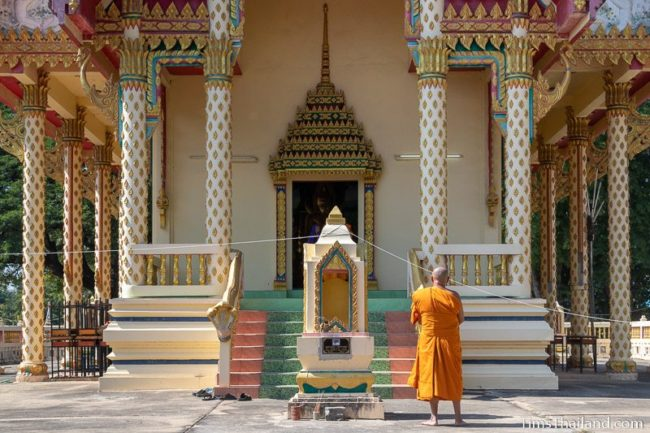 monk standing in front of the ubosot