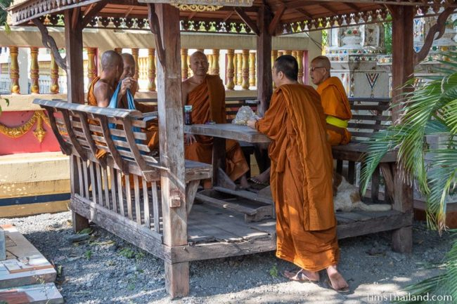 monks chatting while waiting in front of the ubosot