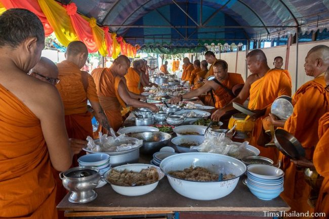 monks taking food off a table