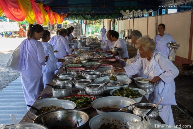women wearing white taking food off a table