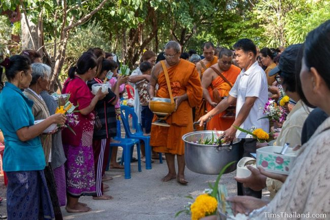 monks collecting alms from a line of people