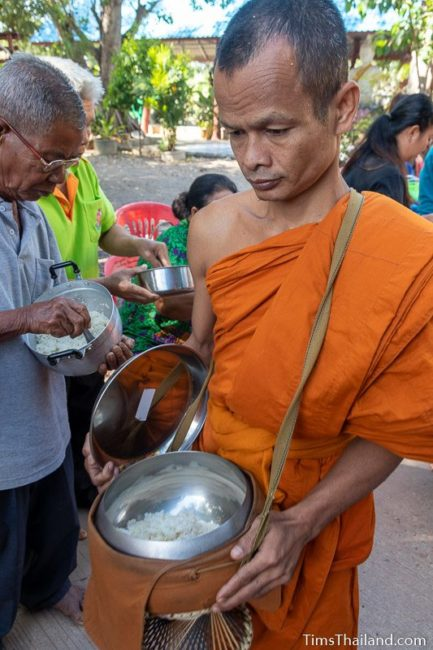 monk collecting alms from a line of people
