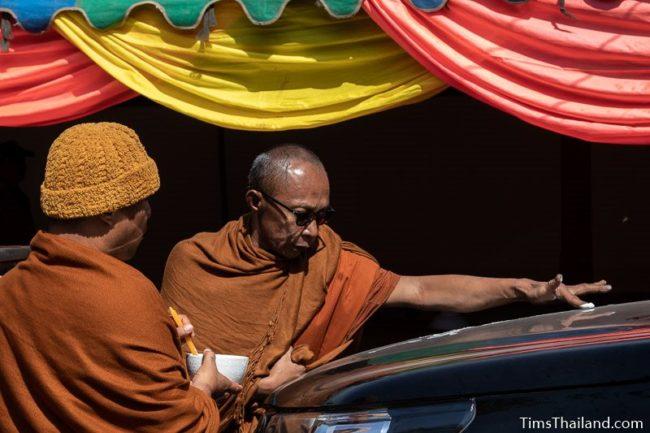 monk writing a yant on a car hood